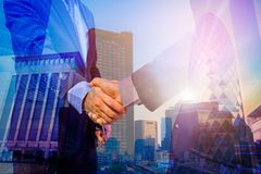 Double exposure photo. Photo mix building city and Shake hands. They are join hands mean teamwork and spirit beside building background. Photo concept for stock photos