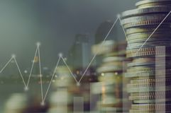 Double exposure pile of coins and night city, concept in growth, save, finance, account,capital banking  and investment. In business Stock Image