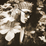 Double Exposure Portrait of a Beautiful Hippie Girl and Flowers. Double exposure portrait of a beautiful girl and flowers. Monochrome portrait of a young woman Stock Photo