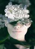 Double exposure portrait. Dream like double exposure portrait of young woman combined with photograph of white lilac flowers Royalty Free Stock Photos