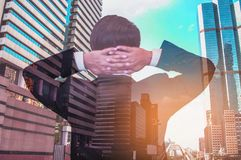 Double exposure Portrait of a gentleman standing back in a suit. Background is skyscrapers. royalty free stock photo