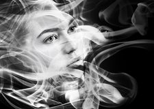 Double exposure portrait of woman and smoke. Female face dissolving stock photo