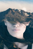 Double exposure portrait. Of young woman covering here eyes with hair combined with photograph of mountain Stock Photo