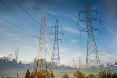 Double Exposure of Pylons in a field. Electrical tower pylon with wires on a blue sky with clouds Stock Image
