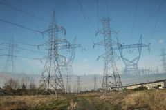Double Exposure of Pylons ina field. Electrical tower pylon with wires on a blue sky with clouds Royalty Free Stock Images