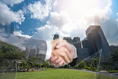Double exposure of shaking hand business people for success deal stock photography