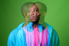 Double exposure shot of young African man against green background. Studio shot of young African man wearing blue jacket with pink shirt against green background stock photos