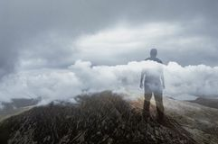A double exposure of a silhouette of a man looking out on a mountain covered in storm clouds royalty free stock photos