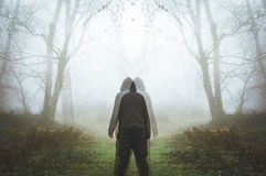 A double exposure of a spooky hooded figure looking two ways. In a foggy, winter eerie forest.  royalty free stock photography