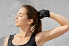 Double exposure and sport concept. Healthy woman with dark pony tail, dressed in t shirt, keeps eyes shut, wears special gloves fo stock photos