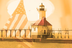 Double exposure St. Joseph north pier lighthouse along shoreline of Lake Michigan with American flag background Stock Image