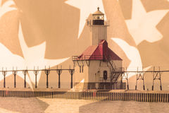 Double exposure St. Joseph north pier lighthouse along shoreline of Lake Michigan with American flag background Stock Images