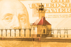 Double exposure St. Joseph north pier lighthouse along shoreline of Lake Michigan with hundred dollar bill background Royalty Free Stock Images