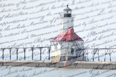 Double exposure St. Joseph north pier lighthouse along shoreline of Lake Michigan with old writing background. United States vintage nautical coastline landmark Royalty Free Stock Photography