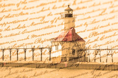Double exposure St. Joseph north pier lighthouse along shoreline of Lake Michigan with old writing background Royalty Free Stock Photography