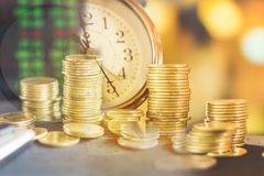 Double exposure stack of coins ,clock and stock market screen ,saving,investment concept stock images