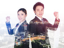 Double exposure of successful business man and woman with arm ra. Double exposure of successful business men and women with arm raised with a city background Royalty Free Stock Photography