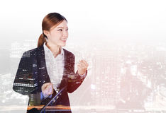Double exposure of Successful business woman with arm raised wit stock photo