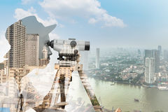 Double exposure of surveyor working with theodolite against bang Royalty Free Stock Photography