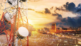 Double exposure telecommunication towers with TV antennas and satellite dish in sunset, with city background. S Stock Photo