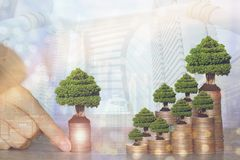 Double exposure of Trees growing on coins money on city backgrou stock photo
