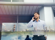 Double exposure of urban businessman with phone device and indus Royalty Free Stock Images