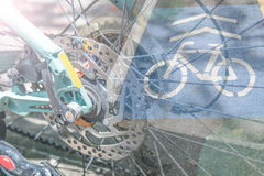 Double exposure wheel bike with bike sign on the bike path Royalty Free Stock Images
