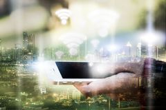 Double exposure of woman hand hold and touch screen with wifi icon. Smartphone and city night as communication and technology con. Cept royalty free stock photo