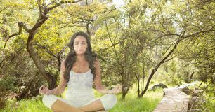 Double exposure of woman meditating in forest. Digital composite of Double exposure of woman meditating in forest Stock Photo