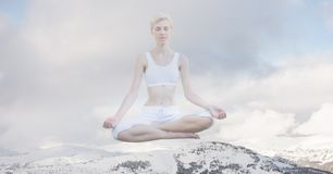 Double exposure of woman meditating on snow covered mountain Stock Photo