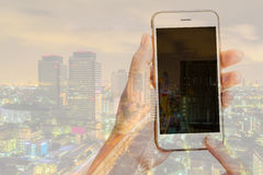 Double exposure of woman using her smart phone and city skyline Stock Image