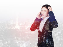 Double exposure of worried business woman talking on smartphone with a city. Background Stock Photos