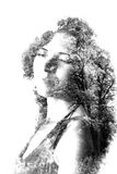 Double exposure of young beautiful girl among the leaves and trees. Portrait of attractive lady combined with photograph of tree. Stock Photos
