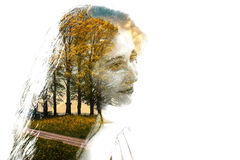 Double exposure of young beautiful girl among the leaves and trees. Portrait of attractive lady combined with photograph of tree. Stock Image
