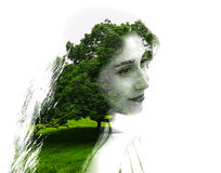 Double exposure of young beautiful girl among the leaves and trees. Portrait of attractive lady combined with photograph of tree. Royalty Free Stock Photography