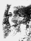 Double exposure of young beautiful girl among the leaves and trees. Portrait of attractive lady combined with photograph of tree. Creative. Effect of double Royalty Free Stock Photography