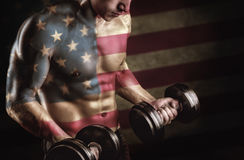 Double Exposure. Of a young muscular man with dumbbells and American flag Stock Photography