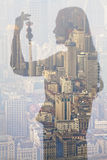 Double exposure of young woman holding Chinese ornament over cityscape Royalty Free Stock Photos
