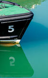 Double Five. The reflection of a boat on the harbour water with the number five Stock Photos