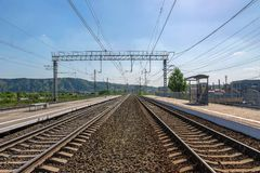 Empty railway station on a summer day. Double free railroad tracks at the station somewhere around the hills on a hot sunny day, waiting for the train Royalty Free Stock Photo