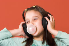 Double fun. Young girl enjoying the music and making a bubble from chewing gum Royalty Free Stock Photography