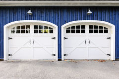 Double garage doors. Two white garage doors with windows on blue house Royalty Free Stock Images