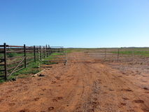Double gates and fence to stockyard road Royalty Free Stock Image