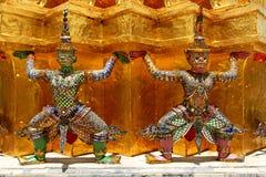 Double giant ramayana statues liftting golden pagoda. At Wat Pra kaew, Grand Palace, Bangkok, Thailand royalty free stock image