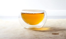 Double glass tea cup filled with green tea. On vintage aged paper Royalty Free Stock Image