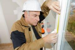 Double glazing installer measuring window. Double glazing installer measuring the window stock photos