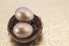 Double gold retirement nest eggs reward solving savings puzzle Royalty Free Stock Images
