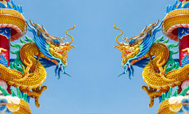 Double golden dragon statue on blue sky background Royalty Free Stock Image