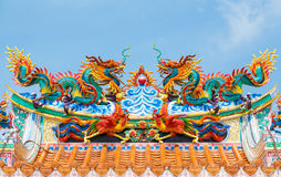 Double golden dragon statue on blue sky background Royalty Free Stock Photo