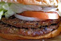 Double Hamburger. Closeup of two charcoal broiled hamburger patties on a sesame seed bun with lettuce, tomato and onion stock image